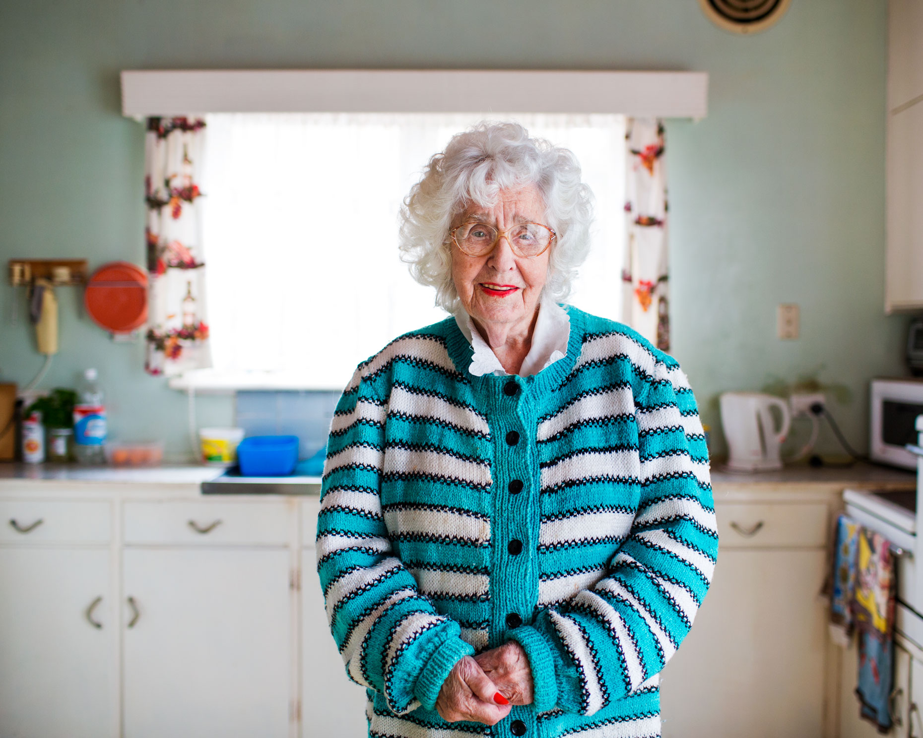 Old lady in colorful cardigan in kitchen