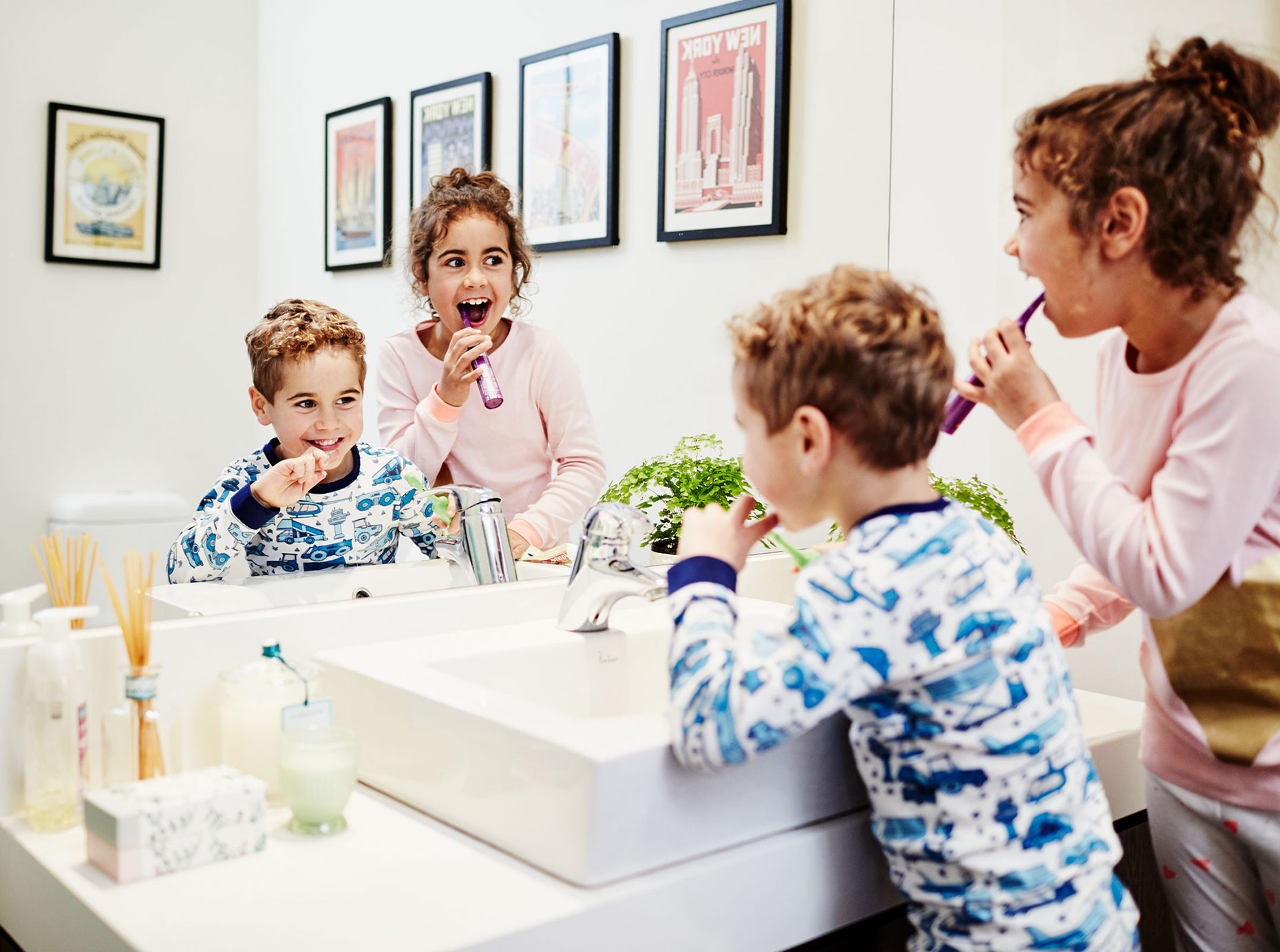 Kids brushing teeth in front of bathroom mirror