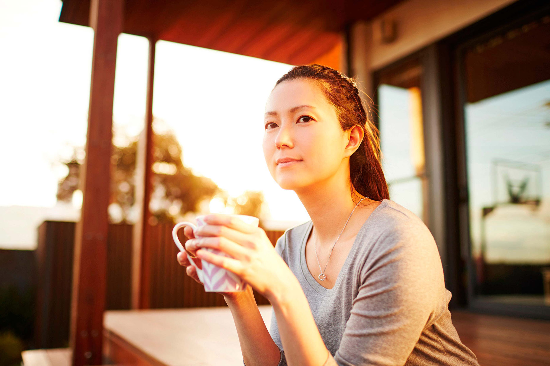 young woman enjoying coffee at sunset